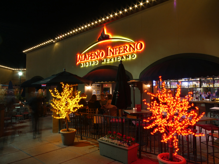 Jalapeno Inferno Mexican restaurant in Scottsdale and Peoria Arizona showing the outside of the restuarant and patio seating with lit trees